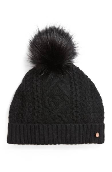 Cable-knit beanie with faux fur pompom for a chic après-ski look. Details at une femme d'un certain age.