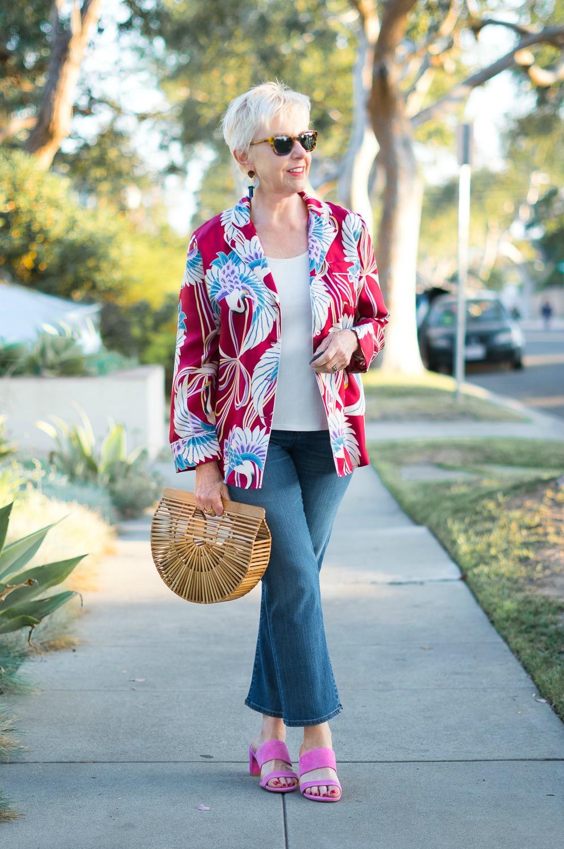 Style blogger Susan B. wears an Asian print silk jacket, jeans, and pink suede slide sandals. Details at une femme d'un certain age.