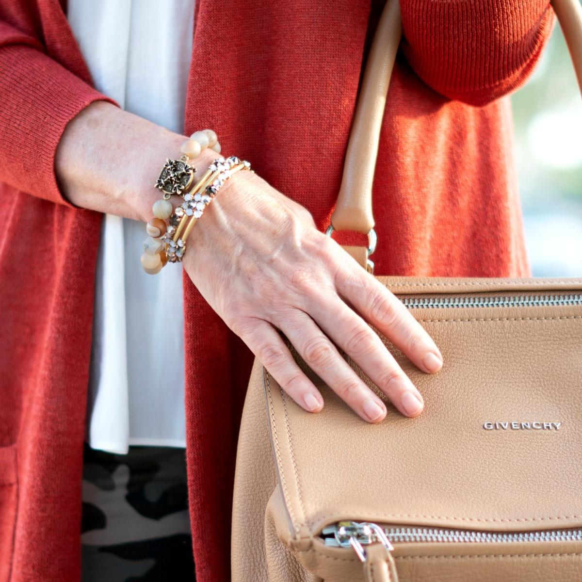 Detail: gold-tone bracelets and Givenchy Pandora bag. Details at une femme d'un certain age.