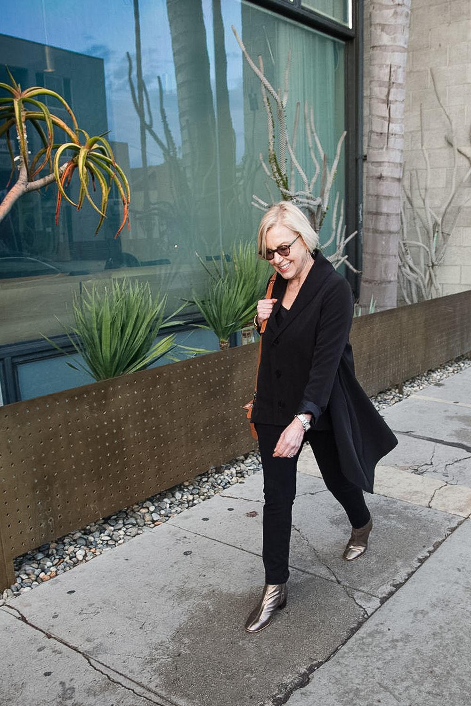 Susan B. of une femme d'un certain age wears a black Ruti jacket and metallic boots.