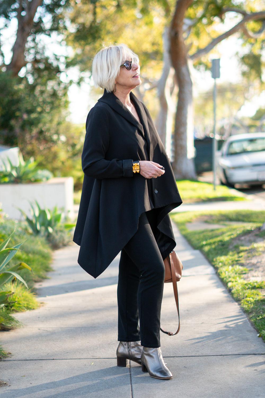 Susan B. of une femme d'un certain age wears a black draped jacket, black pants, Hermes collier de chien cuff and metallic boots.