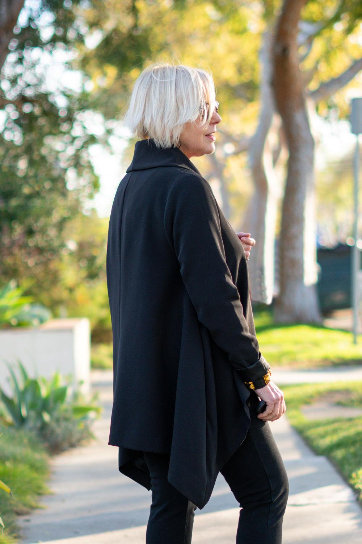 Back view of black draped Ruti jacket worn by Susan B. of une femme d'un certain age.