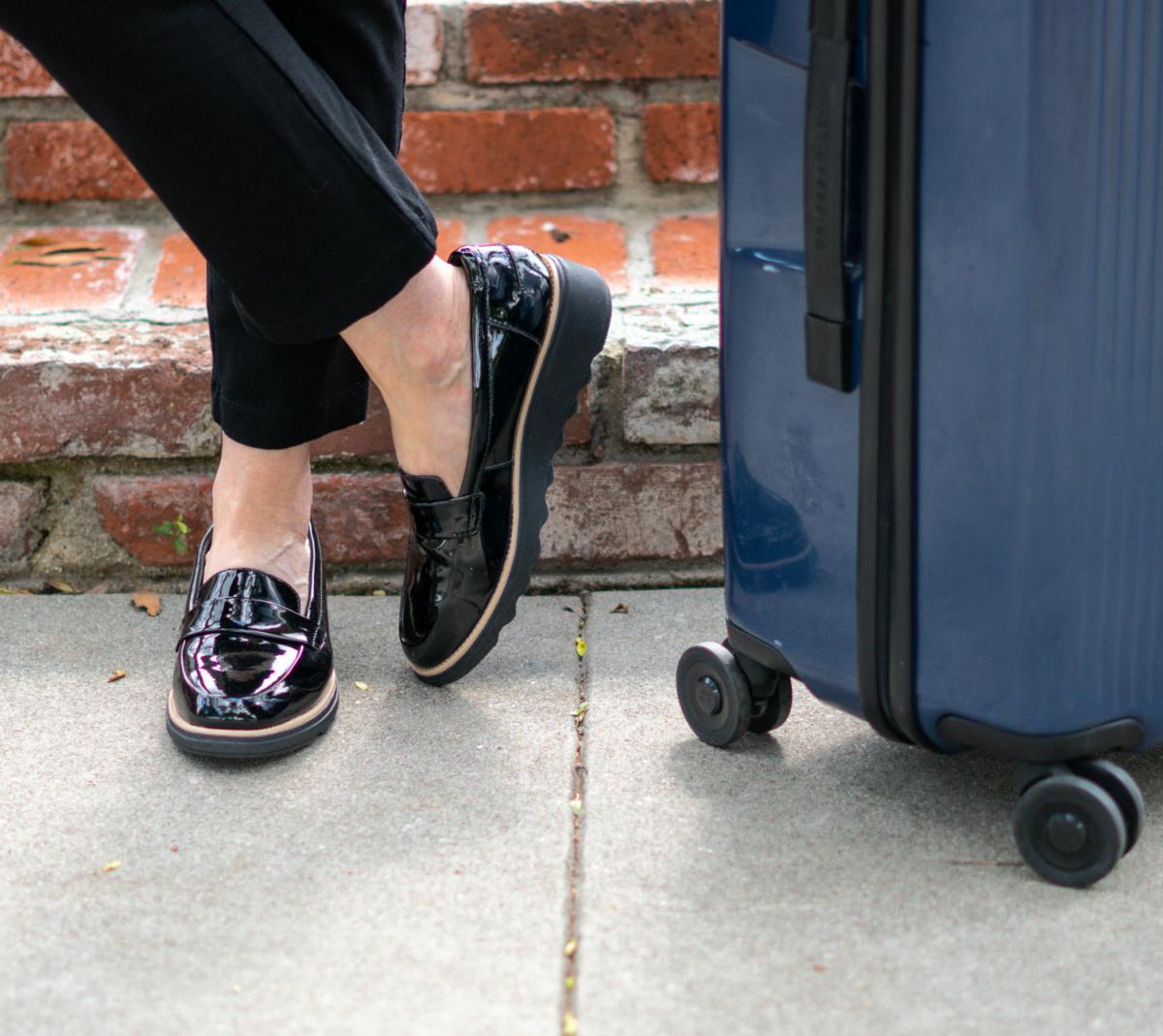 Detail: Susan B. of une femme d'un certain age wears Clark's patent leather loafers.