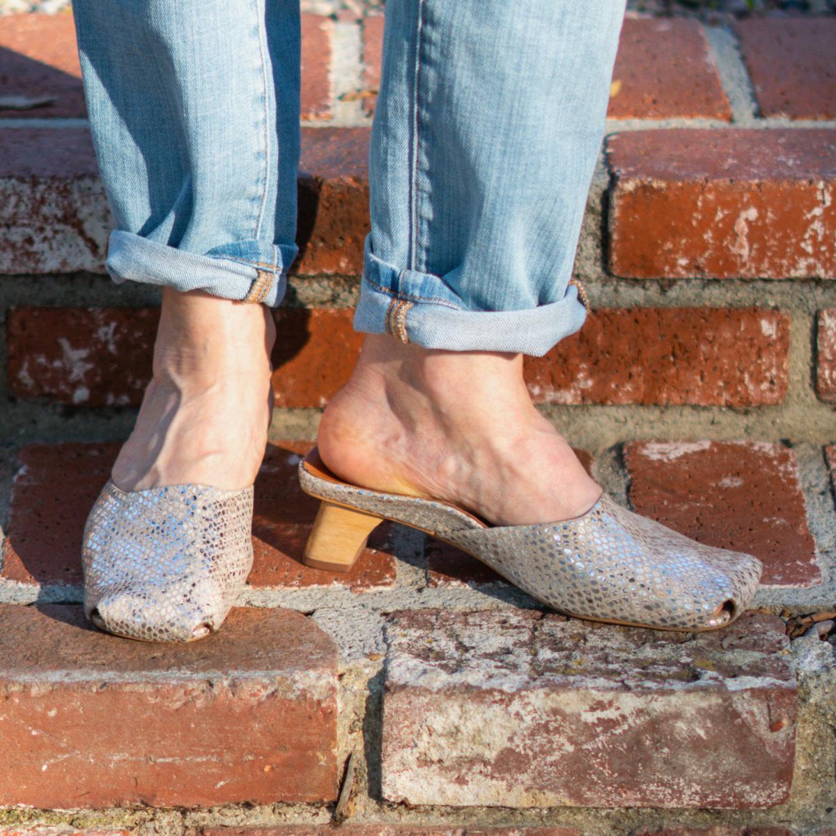 Detail: Susan B. of une femme d'un certain age wears L'Amour des Pieds mules and cuffed jeans.