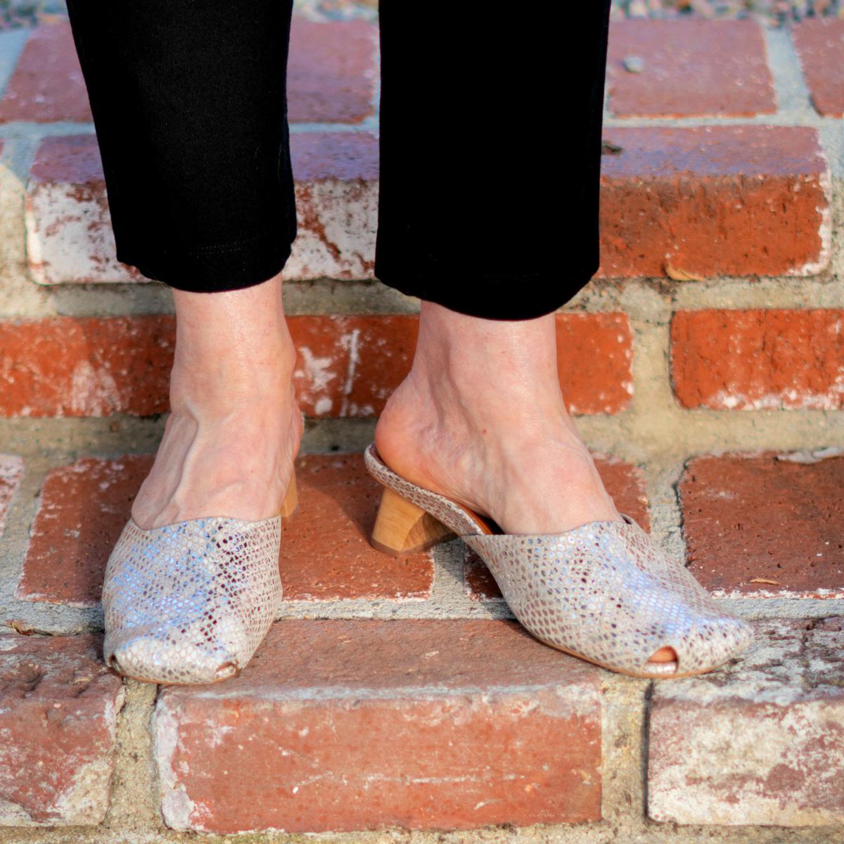 Detail: Susan B wears black ankle pants and L'Amour des Pieds metallic mules. Info at une femme d'un certain age.