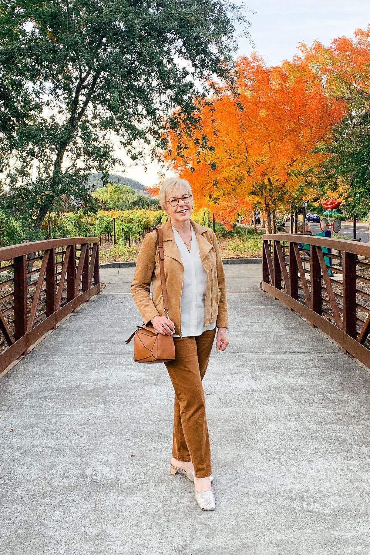 Susan B. of une femme d'un certain age on a bridge wearing a faux suede jacket and brown pants.