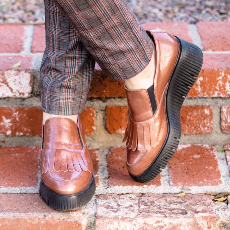 Detail: Susan Blakey wears Wonders platform loafers in copper patent leather. Info at une femme d'un certain age.