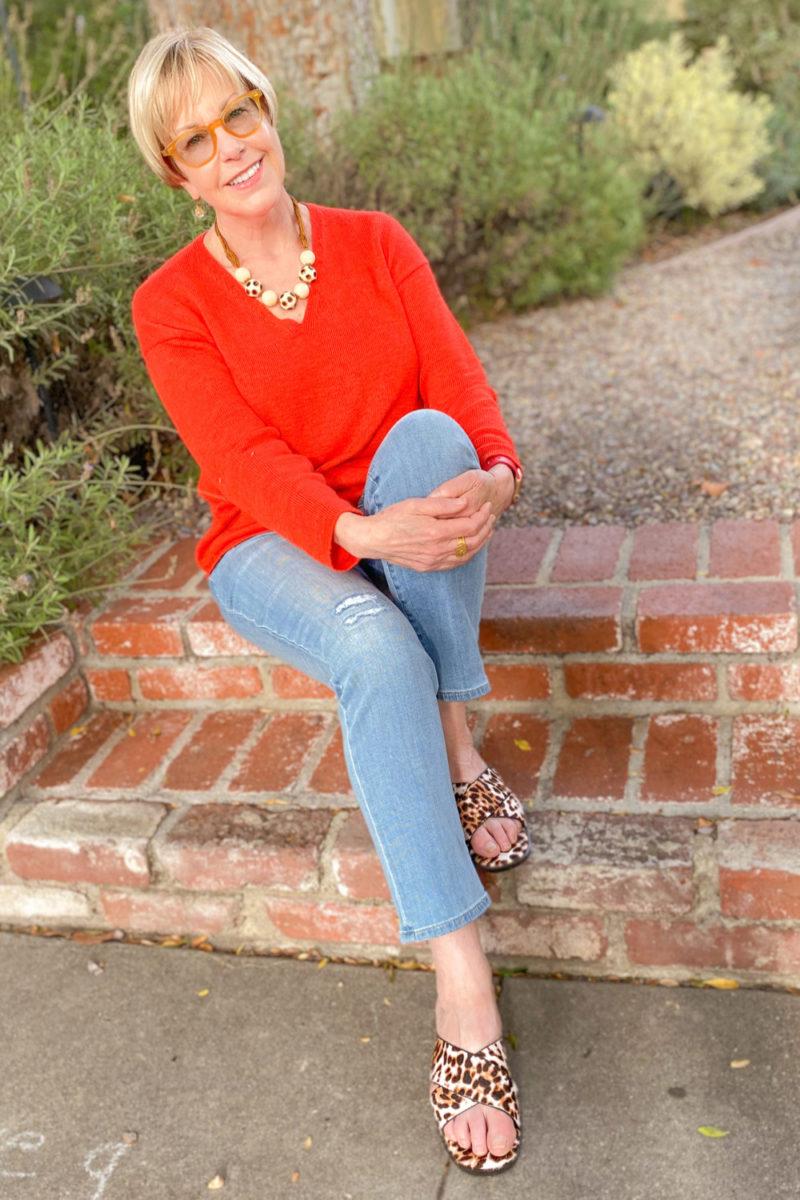 Susan B. wears a red summer sweater, light wash jeans and leopard slide sandals. Details at une femme d'un certain age.
