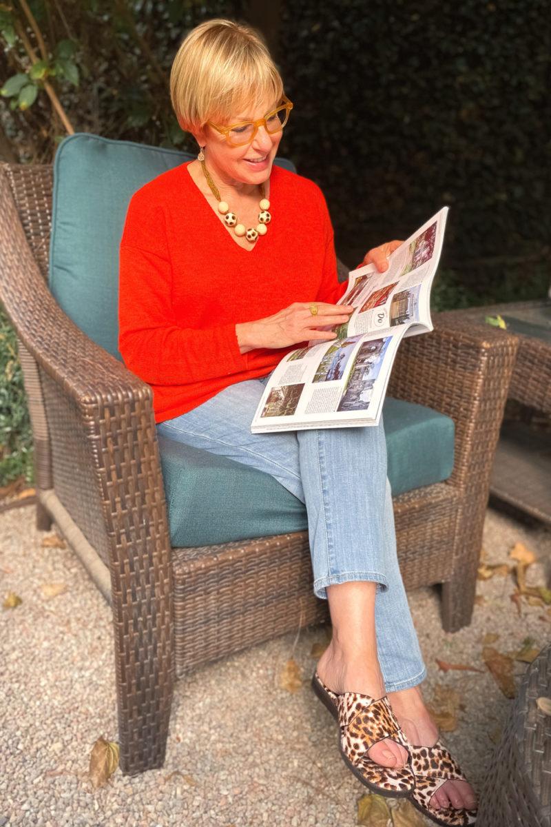 Susan B. of une femme d'un certain age wears a red summer sweater, light wash jeans and leopard print sandals.