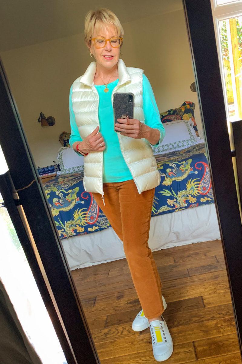 Susan B. wears brown corduroy pants, a puffer vest, blue tee and white sneakers. Details at une femme d'un certain age.