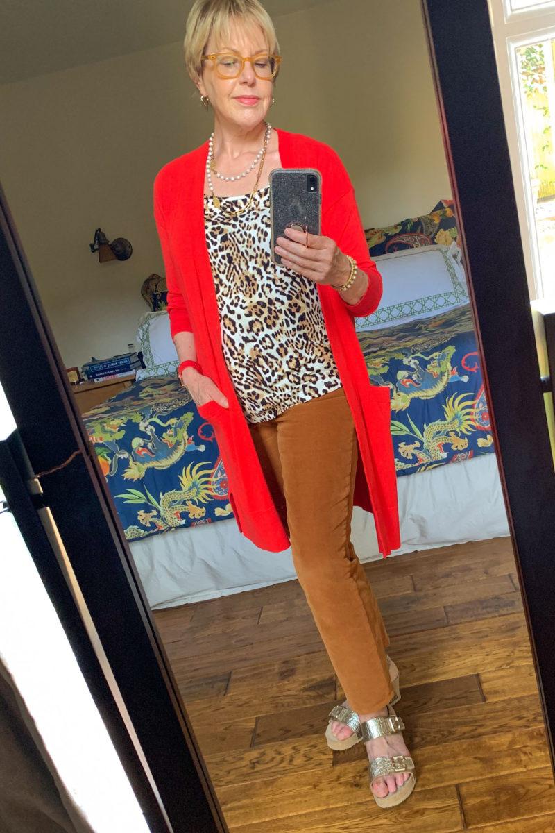 Susan B. wears a red cardigan, leopard print tank, brown corduroy pants and gold wedge sandals. Details at une femme d'un certain age.