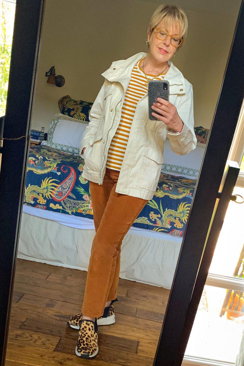 Susan B. wears brown straight leg corduroy pants, a striped tee, utility jacket and leopard sneakers. Details at une femme d'un certain age.