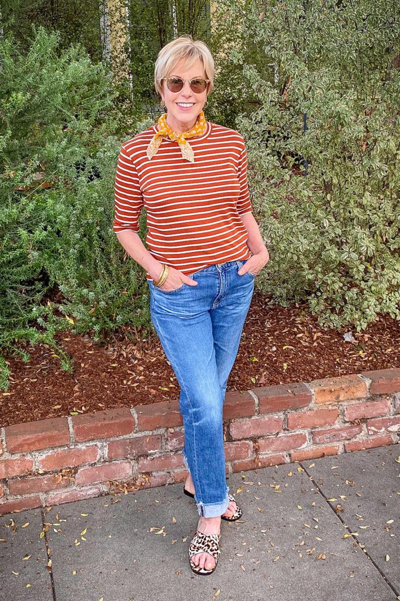 Fall outfit for warm weather: Susan B. wears a striped tee, bandana neckerchief, boyfriend jeans, and leopard slide sandals. Details at une femme d'un certain age.