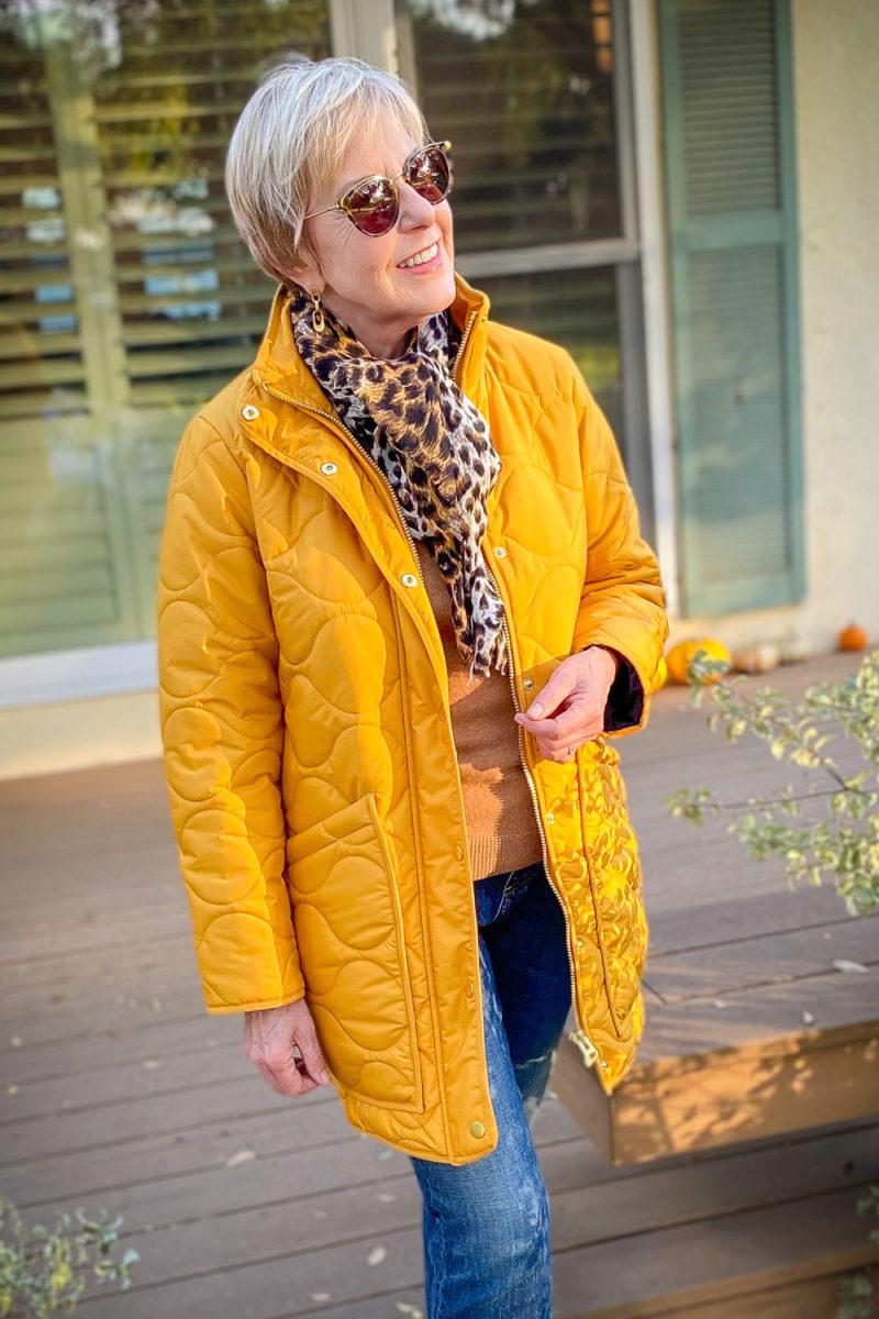 Susan B. wears a gold J.Crew puffer jacket with a leopard print scarf. Details at une femme d'un certain age.