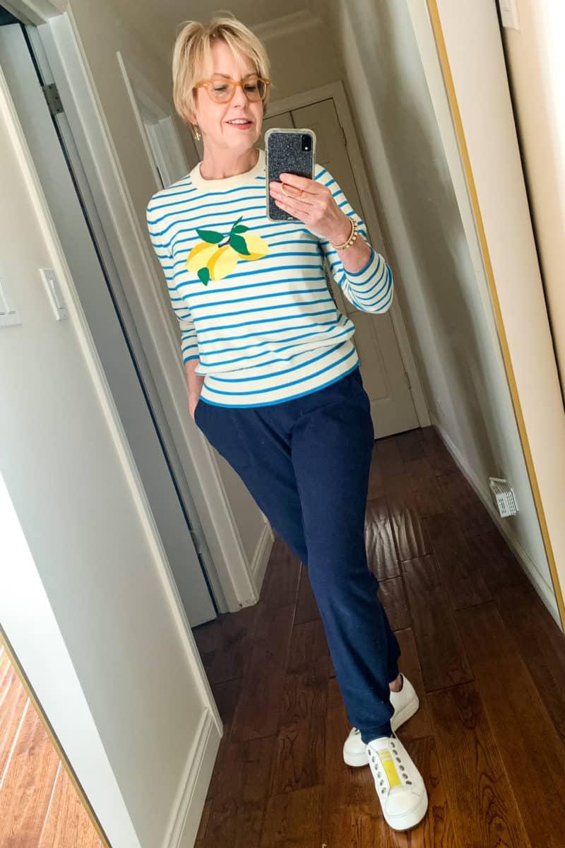 Susan B. wears a lemon print stripe sweater, navy joggers and sneakers. Details at une femme d'un certain age.