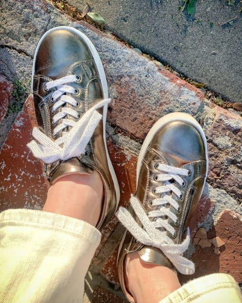 Detail: Susan B wears bronze Sole Bliss zip sneakers.