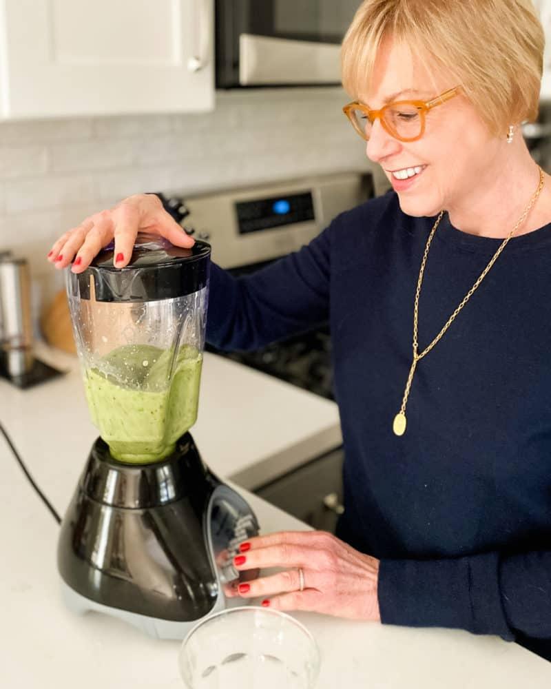 Susan B. makes a kale smoothie in a blender. Details at une femme d'un certain age.