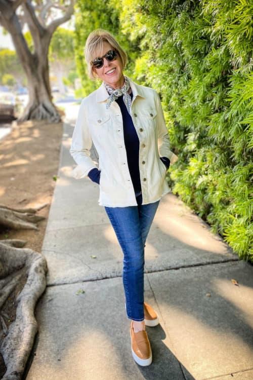 Susan B. wears an elongated cream denim jacket, navy sweater, slim jeans and platform sneakers.