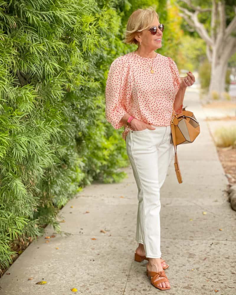Susan B. wears a Samsoe Samsoe polka dot top, J.Crew white jeans, Vince sandals, and Loewe small puzzle bag.