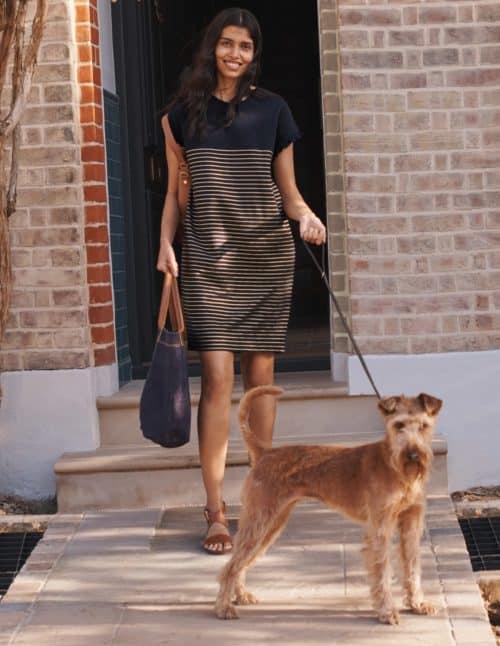 woman walking dog wearing Boden striped tee shirt dress.