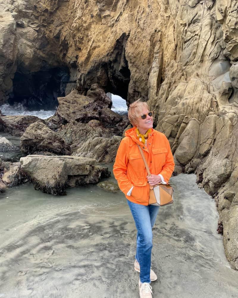 Susan B. at Pfeiffer Beach wearing an orange windbreaker and blue jeans.