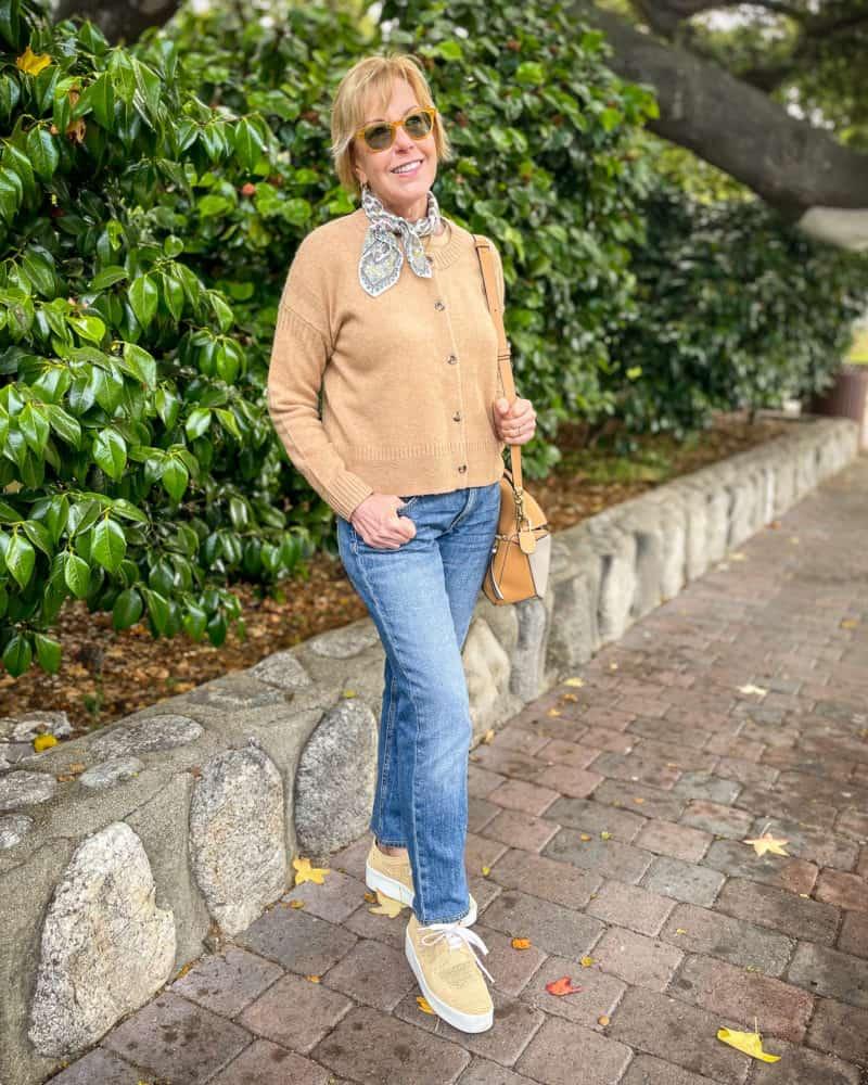 Susan wears a camel cardigan, bandana, jeans and raffia oxfords.