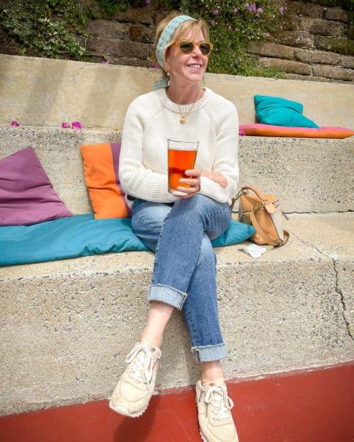 Susan B. enjoying a beer at Nepenthe. Wearing a Madewell bandana, Jenni Kayne cotton fisherman sweater, AG boyfriend jeans.