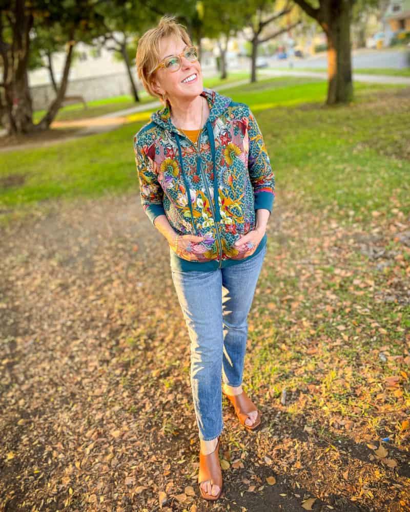 Susan B. wears a colorful hoodie outfit: Johnny Was hoodie, rag & bone jeans, Frame sandals.