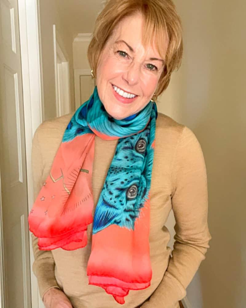 Susan B. wears the Emma J. Shipley Snow Leopard silk scarf in the Spring palette.